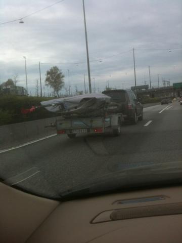 Bil med släp. På släpet står ännu ett släp, med en liten segeljolle på.